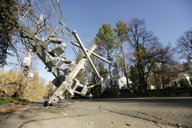 A utility pole dangles near E. 23rd Ave. and S. Garfield St., after a wind storm, Wednesday, Nov. 18, 2015, in Spokane, Wash. (Young Kwak/Pacific Northwest Inlander)