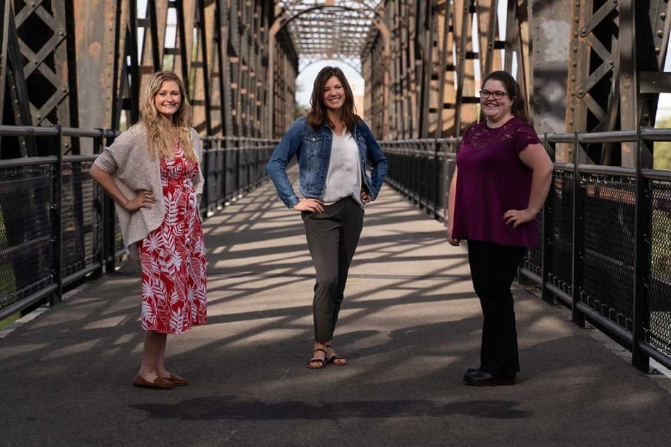 Three of the Pharmacy Residency Students stand on a bridge together